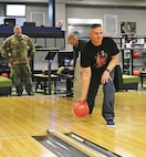 Pfc. Joseph Duda, Headquarters and Headquarters Battalion, 1st Infantry Division, locks eyes on the bowling pins as he gears up to fling the bowling ball down the alley for the meet-and-greet Jan. 18 at Custer Hill Bowling Center.