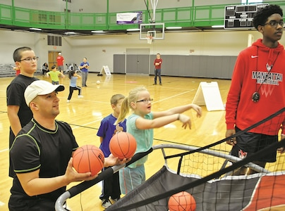 Staff Sgt. Johnny Zamorano, left, 601st Aviation Support Battalion, 1st Combat Aviation Brigade, 1st Infantry Division, helps his daughter Katie Compher, 6, in the kid's version of a three-point basketball shoot during the Family Fun Olympics event at Whitside Fitness Center Jan. 20. The family friendly event was suitable for participants from all ages.