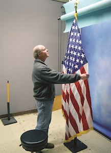 Peter Aiken, visual information specialist at Fort Riley's Visual Information Support Center operated by the Directorate of Plans, Training, Mobilization and Security prepares the American flag used as a prop for command photos. Aiken is the sole employee who takes thousands of Department of the Army photos for promotable Soldiers and command photos for officers across the installation.