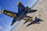 Pilots assigned to the Navy's demonstration squadron fly at an angle over land.