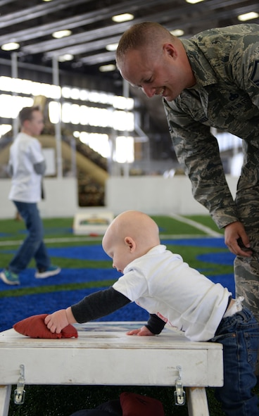 Master Sgt. Michael Cromer, a flight line expeditor assigned to the 28th Aircraft Maintenance Squadron, watches his son, Jonah, play with a bean bag at the Pride Hangar at Ellsworth Air Force Base, S.D., Jan. 29, 2018. B-1 bombers from the 37th Bomb Squadron and Airmen from the 37th Aircraft Maintenance Unit were deployed to Andersen AFB, Guam, to take part in the Continuous Bomber Presence mission. (U.S. Air Force photo by Airman 1st Class Nicolas Z. Erwin)