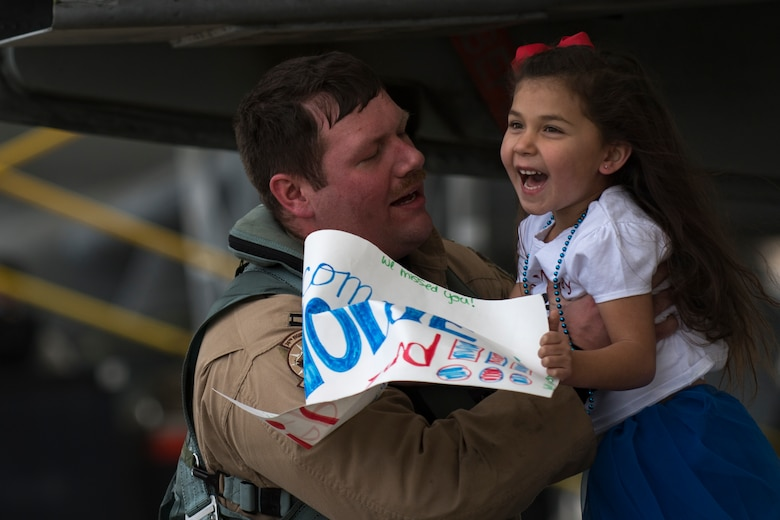 Capt. Brendan Lanphear, 74th Fighter Squadron pilot, lifts his daughter Rownin after returning from a deployment, Jan. 26, 2018, at Moody Air Force Base, Ga. During the seven-month deployment, the 74th FS flew more than 1,700 sorties, employed weapons more than 4,400 times, destroyed 2,300 targets and killed 2,800 ISIS insurgents. (U.S. Air Force photo by Senior Airman Daniel Snider)