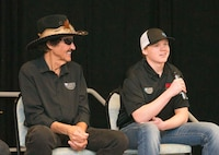 Richard Petty, left, and his grandson, Thad Moffitt, both Nascar drivers, answer questions for Team Ramstein at the Kaiserslautern Military Community Center on Ramstein Air Base, Germany, Jan. 27, 2018. Petty and Moffitt signed memorabilia, posed for pictures with service members and their families, and participated in a question and answer session. (U.S. Air Force photo by Senior Airman Elizabeth Baker)