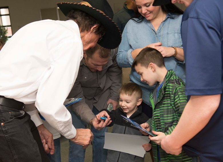 A child receives a toy car which Richard Petty, Nascar legend, signed on Ramstein Air Base, Germany, Jan. 27, 2018. Petty signed memorabilia, took pictures with new Air Force recruits and their families, and participated in a question and answer session in part because the Air Force Recruiting Service sponsors Petty and Richard Petty Motor Sports, which displays the Air Force symbol on car Nascar racecar number 43. (U.S. Air Force photo by Senior Airman Elizabeth Baker)