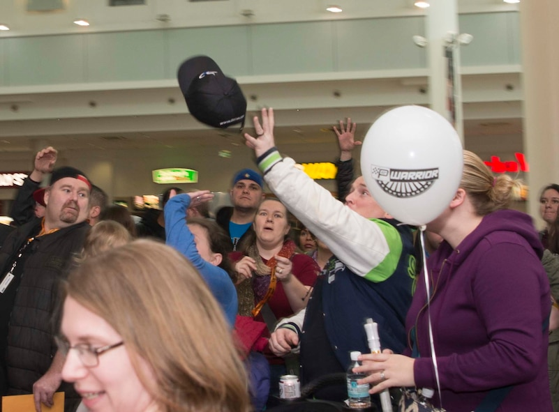 A member of Team Ramstein reaches to catch a free hat while waiting to see Richard Petty, Nascar legend, at a Kaiserslautern Military Community Center event on Ramstein Air Base, Germany, Jan. 27, 2018. The 86th Force Support Squadron, United States Air Force Recruiting Europe, the Kaiserslautern Military Community Center, and Military Auto Source brought Petty to Ramstein to participate in Air Force recruiting and help raise money for Paralyzed Veterans of America. (U.S. Air Force photo by Senior Airman Elizabeth Baker)