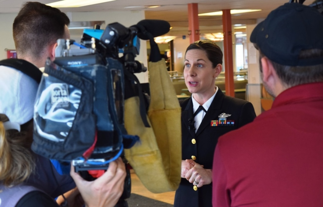 Navy Lt. Cmdr. Erika Schilling, a nurse midwife at Naval Hospital Bremerton, Wash., is interviewed by radio and television reporters in Seattle, Jan. 18, 2018. Shilling was recognized by Washington State Ferries with the Life Ring Award certificate for her life saving efforts on Dec. 2, 2017, when she saved a male passenger's life by administering emergency cardiopulmonary resuscitation for 14 minutes on the Kingston-Edmunds ferry. Navy photo by Douglas H Stutz