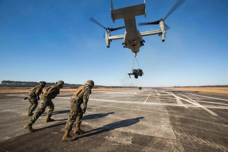 Marines with Landing Support Company, 2nd Transportation Support Battalion, 2nd Marine Logistics Group brace themselves for the high winds produced by a MV-22 osprey as it lifts a 400 gallon M-149 water tank trailer during sling load operations at Camp Lejeune, N.C., Jan. 25, 2018. during sling load operations at Camp Lejeune, N.C., Jan. 25, 2018. The Marines conducted sling load operations to improve their proficiency with loading equipment onto aircraft for transportation. (U.S. Marine Corps photo by Sgt. Chris Garcia)