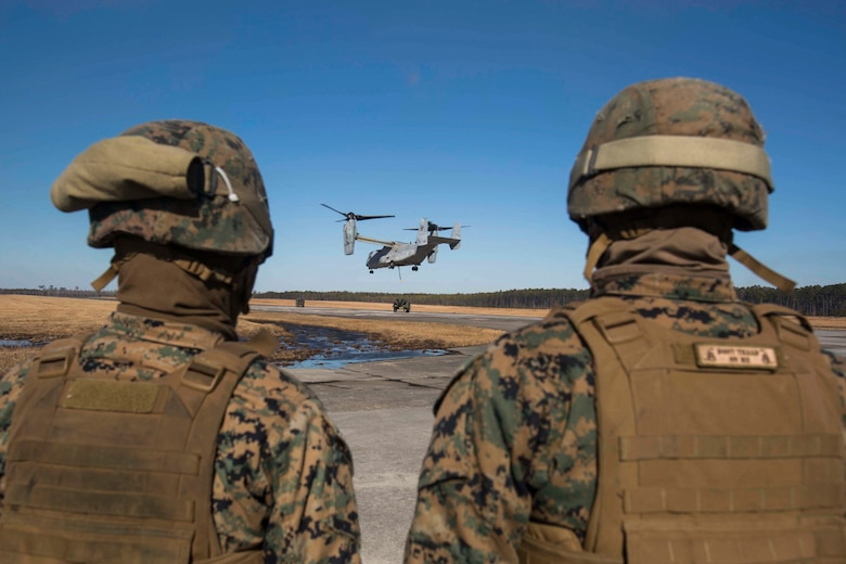 Marines with Landing Support Company, 2nd Transportation Support Battalion, 2nd Marine Logistics Group watch an MV-22 as it prepares to lift and transport a 400 gallon M-149 water tank trailer during sling load operations at Camp Lejeune, N.C., Jan. 25, 2018. The Marines conducted sling load operations to improve their proficiency with loading equipment onto aircraft for transportation. (U.S. Marine Corps photo by Sgt. Chris Garcia)