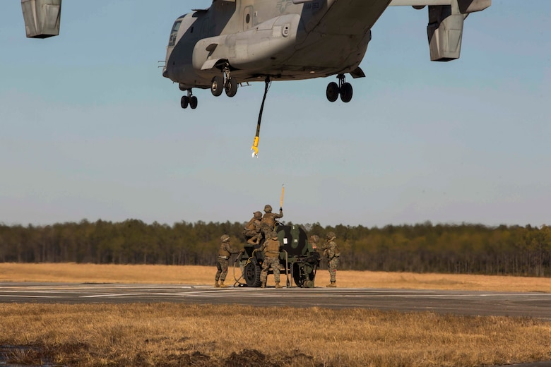 Marines with Landing Support Company, 2nd Transportation Support Battalion, 2nd Marine Logistics Group prepare to attach a 400 gallon M-149 water tank trailer to an MV-22 osprey during sling load operations at Camp Lejeune, N.C., Jan. 25, 2018. The Marines conducted sling load operations to improve their proficiency with loading equipment onto aircraft for transportation. (U.S. Marine Corps photo by Sgt. Chris Garcia)
