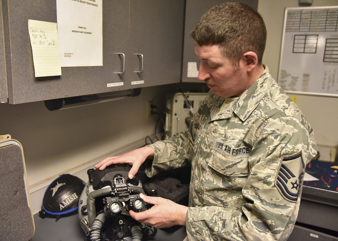Master Sgt. Josh Sells, 114th Operations Support Squadron aircrew flight equipment specialist, attached a digital eyepiece add-on to a helmet at March Air Reserve Base, CA, Jan. 17