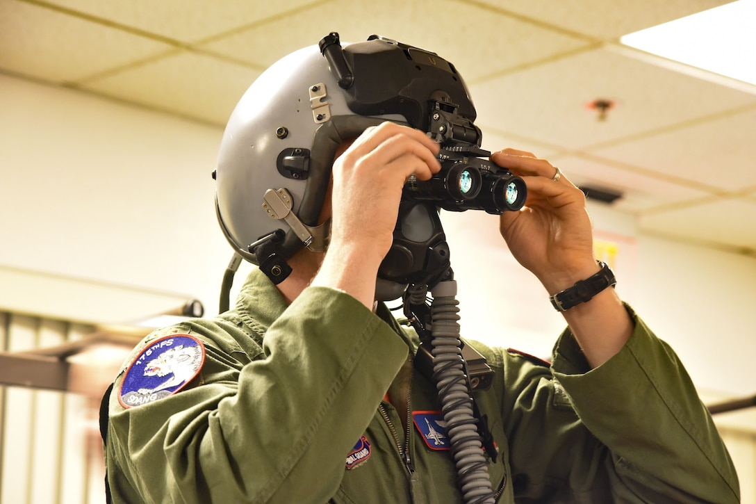 Maj. Casey Minor, 114th FW pilot, tries on the digital eye piece add-on that increases F-16 pilots night flying capabilities at March Air Reserve Base, CA, Jan. 17.