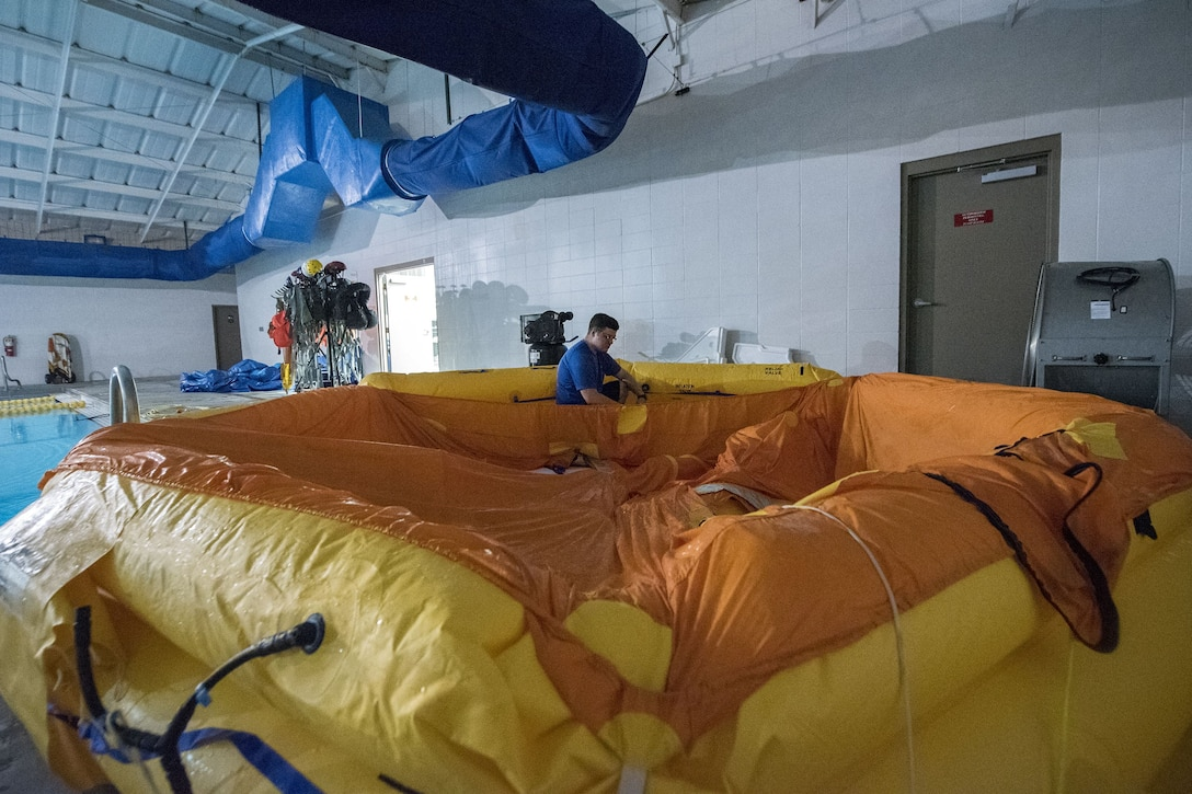 Staff Sgt. Andrew McIntosh, 347th Operations Support Squadron loadmaster, inflates a water raft, Jan. 25, 2018, at Moody Air Force Base, Ga. Aircrew members participated in an underwater survival course to prepare themselves for a situation in which their aircraft were to crash in the water. (U.S. Air Force photo by Airman Eugene Oliver)