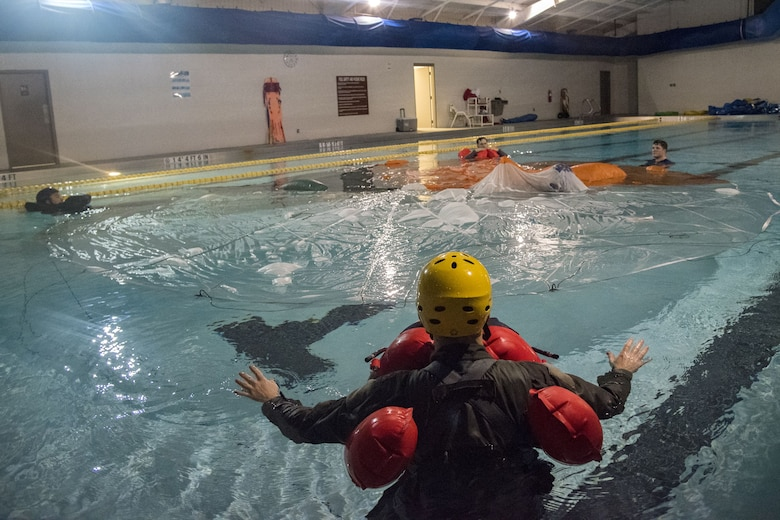 Aircrew members float in a pool surrounding a parachute, Jan. 25, 2018, at Moody Air Force Base, Ga. Aircrew members participated in an underwater survival course to prepare themselves for a situation in which their aircraft were to crash in the water. (U.S. Air Force photo by Airman Eugene Oliver)