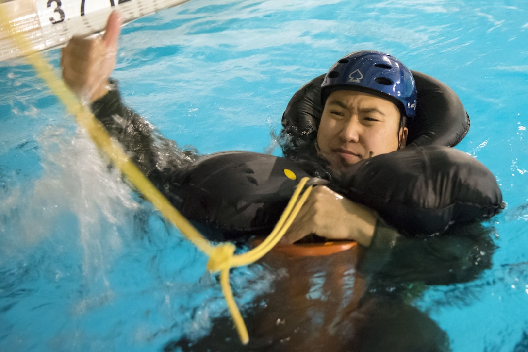 Maj. Albert Chang, 75th Fighter Squadron A-10C Thunderbolt II pilot, gives a thumbs up while floating in a pool, Jan. 25, 2018, at Moody Air Force Base, Ga. Aircrew members participated in an underwater survival course to prepare themselves for a situation in which their aircraft were to crash in the water. (U.S. Air Force photo by Airman Eugene Oliver)