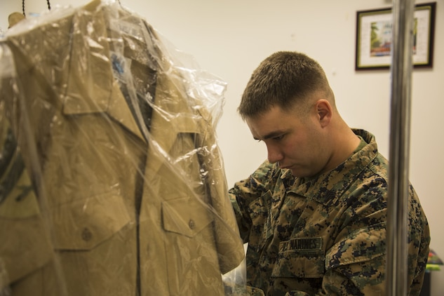 A U.S. Marine stationed on Marine Corps Air Station Yuma, Ariz. looks at his altered uniforms at the station's dry-cleaners Jan. 10, 2017. The station dry-cleaners is a service provided by the Marine Corps Exchange (MCX) to Marines and civilians, which provides them the opportunity to get their garments cleaned, pressed, fitted, altered or a combination of services if needed. (U.S. Marine Corps photo taken by Cpl. Isaac Martinez)