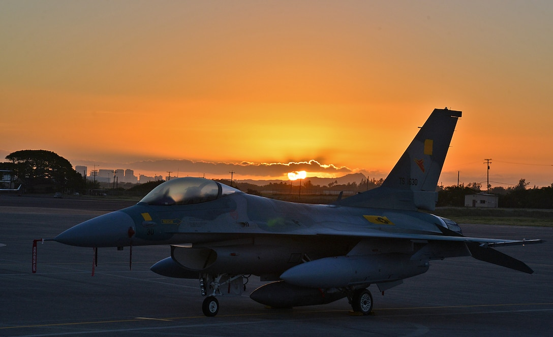 An Indonesian F-16 sits on the tarmac at Hickam Air Force Base, Hawaii, with the sun rising over Diamond Head and downtown Honolulu on Pearl Harbor Day, Dec. 7, 2017. U.S. Air Force Air National Guard pilots along with maintainers from the Ogden Air Logistics Complex spent several days getting six regenerated F-16s from Utah to Indonesia.  (U.S. Air Force photo by Alex R. Lloyd)