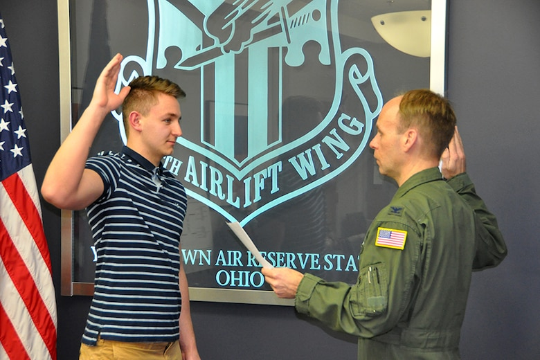 Robert Adler, a new recruit to the 910th Security Forces Squadron, holds an Air Force Reserve sign after taking the oath of enlistment to become a Reserve Citizen Airmen here, Jan. 29, 2018.