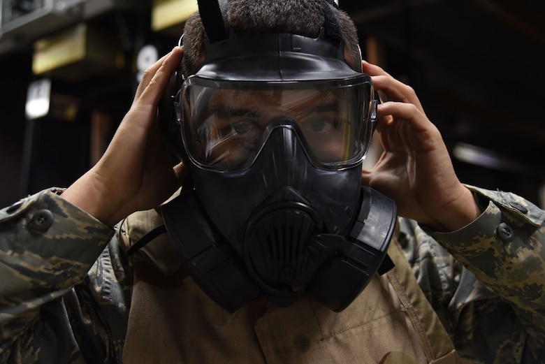A U.S. Airmen puts on a gas mask during an M4 carbine qualification course at Shaw Air Force Base, S.C., Jan. 25, 2018.