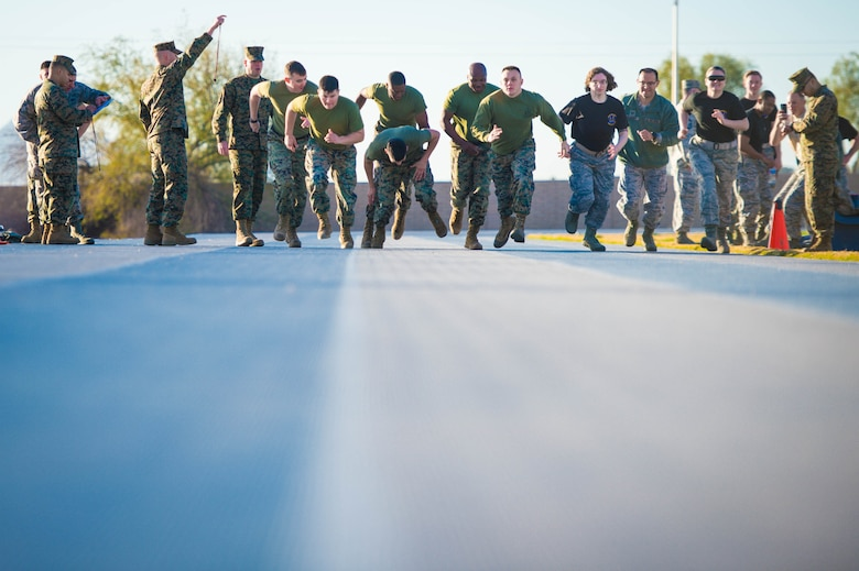 Airmen and Marines run during a combat fitness test challenge at Luke Air Force Base, Ariz., Jan. 26, 2018. The CFT, a Marine Corps physical fitness requirement, started with an 880 yard sprint before moving on to several other combat-related tasks. The challenge between Airmen and Marines was held to build esprit de corps between the two services. (U.S. Air Force photo/Staff Sgt. Jensen Stidham)