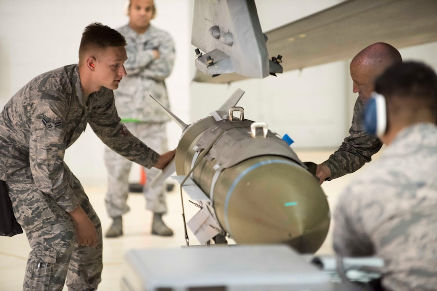 Weapons loaders prepare to load a GBU-31 Joint Direct Attack Munition onto an Edwards jet in the Fourth Quarter Weapons Load Competition held Jan. 8, 2018. The 412th Maintenance Group's Load Crew of the Year Competition is slated for Feb. 5. (U.S. Air Force photo by Kyle Larson)