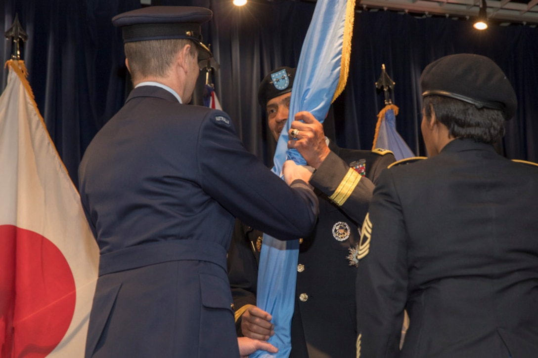 Royal Australian Air Force Group Captain Michael W. Jansen, outgoing United Nations Command (Rear) commander, passes the guidon to U.S. Army General Vincent K. Brooks, United Nations Command, Combined Forces Command and U.S. Forces Korea commanding general during a change of command ceremony