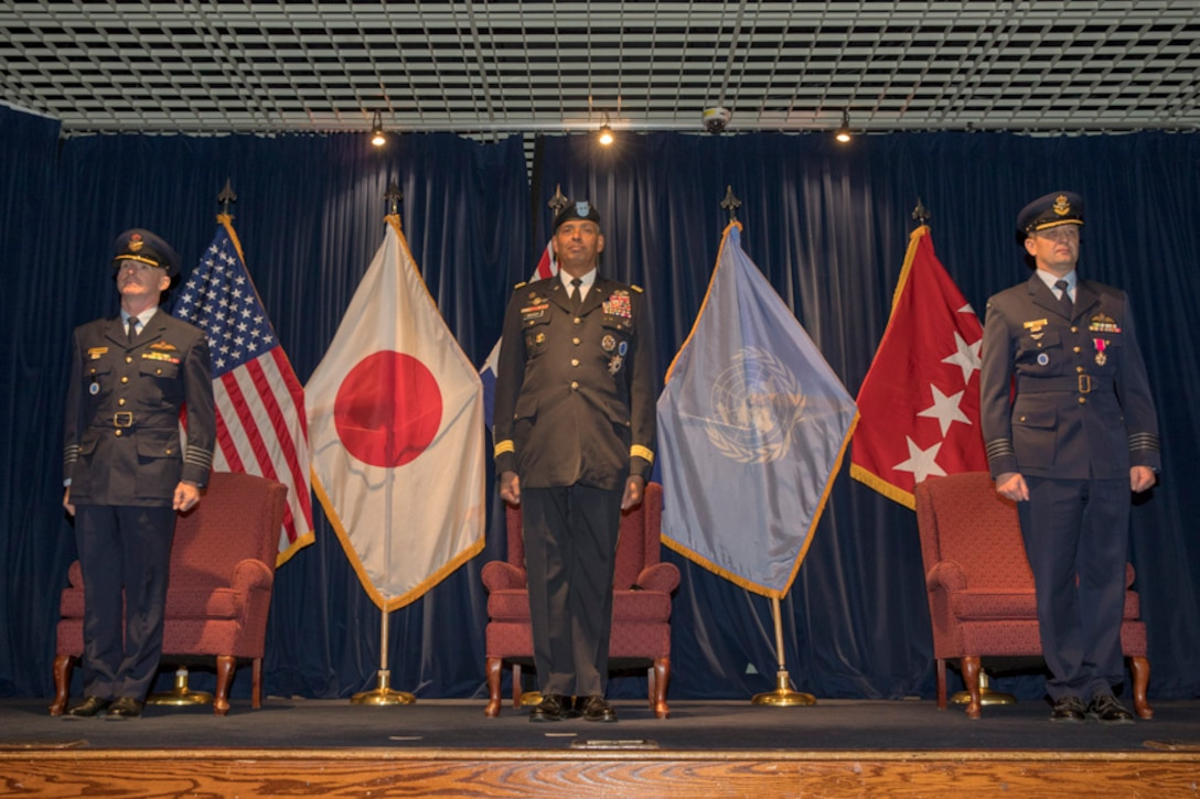 Royal Australian Air Force Group Captain Adam Williams, incoming United Nations Command (Rear) commander, U.S. Army General Vincent K. Brooks, United Nations Command, Combined Forces Command and U.S. Forces Korea commanding general stand in attention during a change of command ceremony
