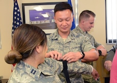 Capt. Christopher Liu, 412th Medical Operations Squadron, applies a tourniquet to Capt. Regina Ortega, 412th MDOS, at the 412th Medical Group's Education and Training building Jan. 29. (U.S. Air Force photo by Kenji Thuloweit)