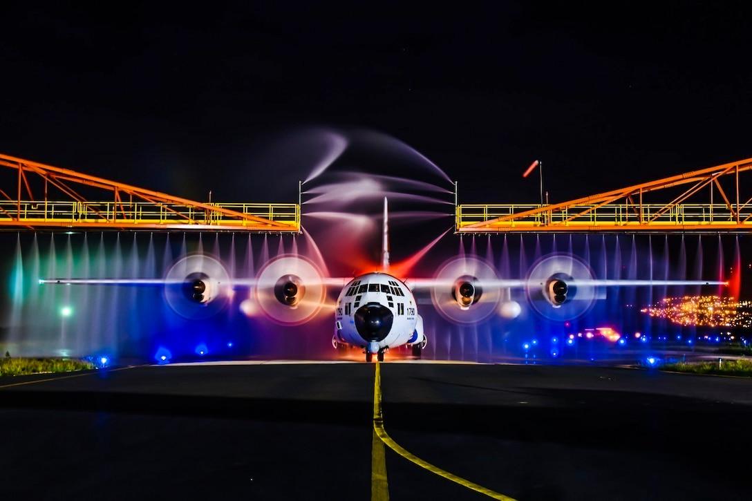 A Coast Guard HC-130 Hercules airplane receives a wash down.