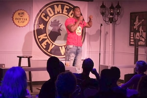 A sailor does stand-up comedy on a stage in Florida.