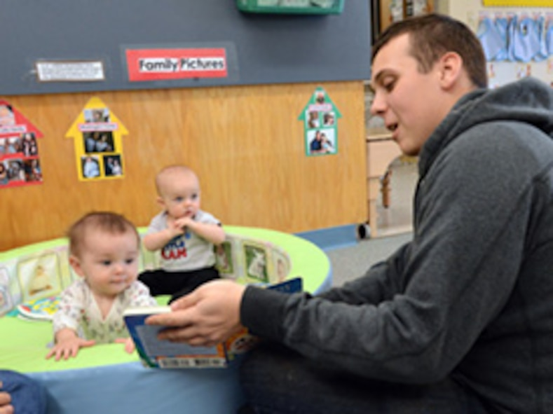 Infants from the Child Development Center East listen to Amn. Jason Keller, with the 552nd Maintenance Squadron as he reads them a book.