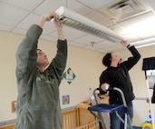 Staff Sgt. Lt Money and Amn. Steven Geiger, both with the 552nd Maintenance Squadron, change lightbulbs in an infant room at the Child Development Center East during a squadron volunteer project Jan. 16.