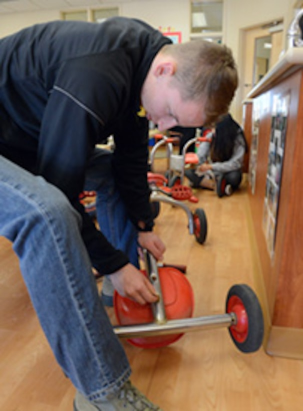 Airman 1st Class Luke Rhoney, 552nd Maintenance Squadron, sands tricycles at the Child Development Center East.