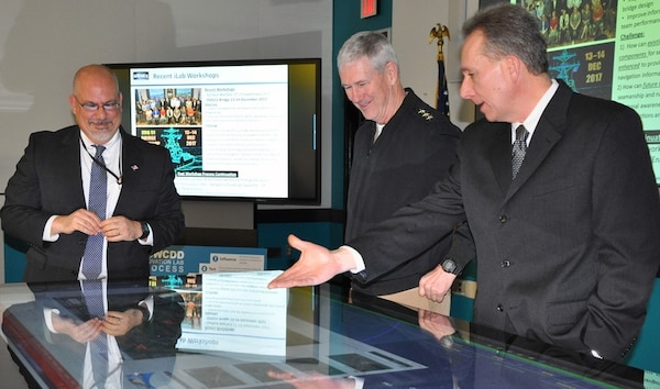 IMAGE: DAHLGREN, Va. (Jan. 16, 2018)  – Naval Surface Warfare Center Dahlgren Division (NSWCDD) Innovation Lab (iLab) Director of Innovation Nelson Mills briefs the Commander of Naval Sea Systems Command (NAVSEA) Vice Adm. Thomas Moore and NSWCDD Technical Director John Fiore on the use of digital collaboration tables as visual aids for surface ships. The collaboration table could provide capabilities to view ship doctrine, navigation tracks, radar information, and Automatic Identification System information for situational awareness. The iLab – equipped with state-of-the-art equipment, services, and trained personnel – opened for business last summer as an intensive collaborative environment where the command's experts work to speed up and maximize corporate innovative solutions across the laboratory.