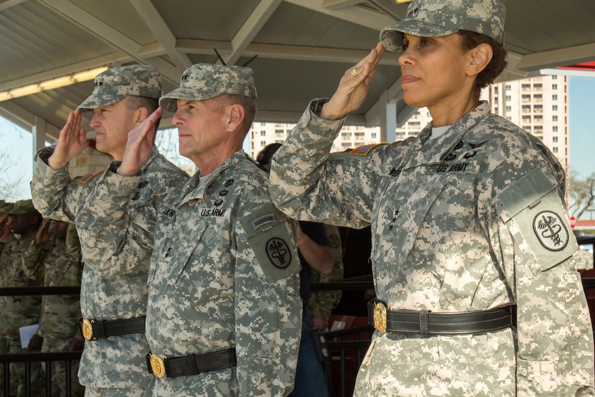 An army Lt. Gen. salutes with two other people during a ceremony.