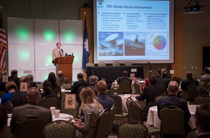 Space and Naval Warfare Systems Center (SSC) Atlantic Executive Director Chris Miller discusses recent achievements at SSC Atlantic during the Charleston Defense Contractors Association's 45th quarterly Small Business and Industry Outreach Initiative (SBIOI) Symposium. SSC Atlantic develops, acquires and provides life cycle support for command, control, communications, computer, intelligence, surveillance and reconnaissance (C4ISR) systems, information technology and space capabilities. A leading-edge Navy engineering center, SSC Atlantic designs, builds, tests, fields and supports many of the finest frontline C4ISR systems in use today, and those being planned for the future.