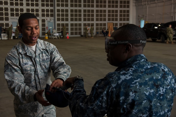 U.S. Air Force Staff Sgt. Dorian Lewis, a 35th Fighter Wing occupational safety technician, hands U.S. Navy Seaman Alston Thornton, a Naval Oceanography Antisubmarine Detachment Misawa aerographer's mate, a hat to wear before he rides a bike while wearing Fatal Vision goggles during the 75th Safety Convention held at Misawa Air Base, Japan, May 24, 2018. These specialized goggles allowed participants to experience how alcohol impairs a person's balance, vision, reaction time and judgment. (U.S. Air Force photo by Airman 1st Class Collette Brooks)