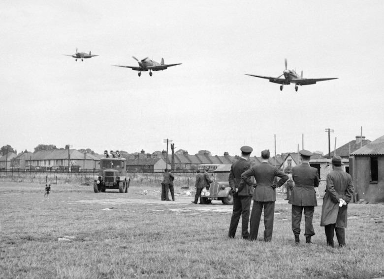 Personnel of No.121 (Eagle) Squadron look on as three Supermarine Spitfire aircraft land after a fighter sweep over northern France at Royal Air Force Rochford in Essex, England August 1942. Some of the accommodation used by the squadron is visible in the background, as are several civilian houses and two RAF vehicles. (Courtesy photo)