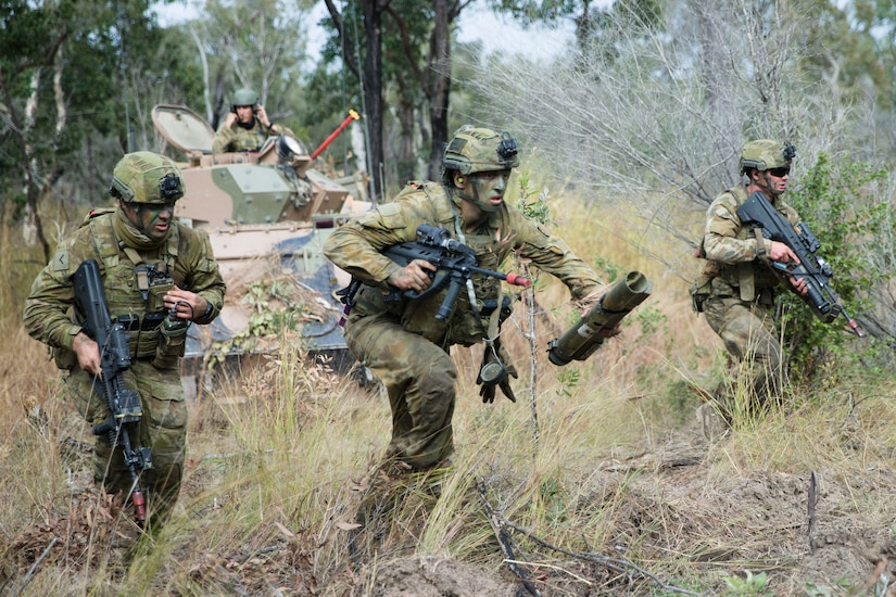 Australian soldiers run through grassland during training.