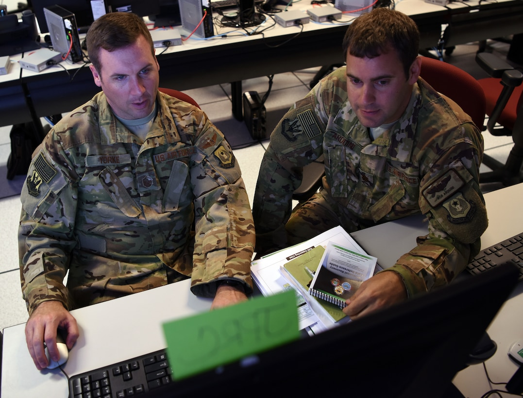 Master Sgt. Brian Yorke, left, Staff Exercise 18-4 Joint Personnel Recovery Center planner, and Maj. Rob Arduini, STAFFEX 18-4 planner, both from Ninth Air Force, discuss JPRC options available for the exercise scenario, June 20, 2018, at Shaw Air Force Base, S.C. The STAFFEX scenario featured a humanitarian assistance effort in the U.S. Africa Command area of responsibility. This is the fourth STAFFEX Ninth Air Force has held since November 2017 as it works toward certification as a Joint Task Force-capable headquarters in the Air Force. (U.S. Air Force photo by Tech. Sgt. Amanda Dick)