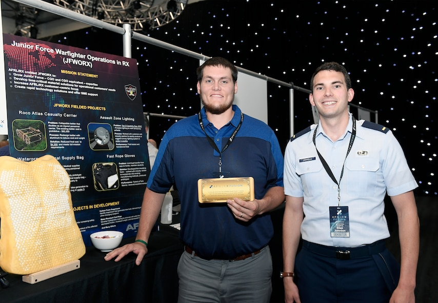 John Bales, a mechanical engineer with AFRL's Materials and Manufacturing Directorate, and 2nd Lt. Elias Johnson, an AFRL materials research engineer, with their Fusion Ticket inviting them to attend a Fusion Ticket event during the week of July 16 at AFWERX Vegas. Initial startup funding, in the range of $150,000, is up for grabs to further assess the teams' technology at the Fusion Ticket event. They were selected for their Flexible Body Armor technology idea. (AFWERX photo/Bobby Mack)