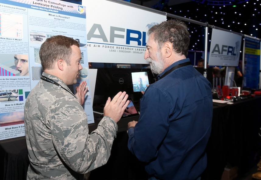 Capt. Glen Pry III, deputy chief, Fuels & Energy Branch, AFRL Aerospace Systems Directorate, explains how lenticular printed technology works and its potential effectiveness in a camouflage, concealment and decoy application to a Fusion Experience event attendee June 21, 2018. (AFWERX photo/Bobby Mack)