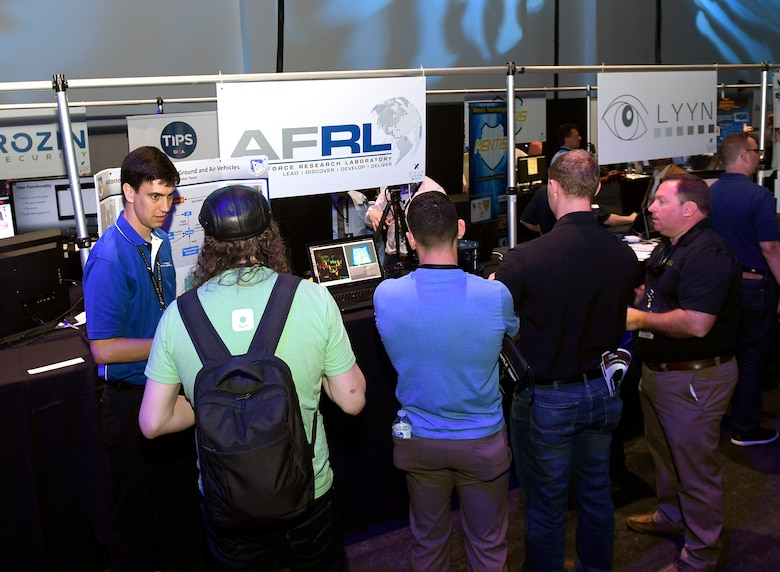Dr. Ryan Sherrill, a research aerospace engineer with the Air Force Research Laboratory Munitions Directorate, discusses autonomy algorithms with attendees at the AFWERX Fusion event. The Munitions Directorate has partnered with the Army Research Laboratory to research algorithms which allow multiple vehicles to autonomously and collaboratively explore and map an unknown space and send the map back to a human operator. (AFWERX photo/Bobby Mack)