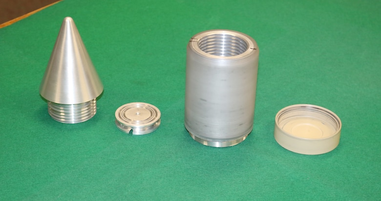 Engineers with the Space and Missiles Combined Test Force at Arnold Air Force Base are developing a telemetry package that will be used to transmit data when launching projectiles at over 25,000 Gs. To accommodate a stand-alone electronics package, an antenna with a detachable radome and multiple integrated sensors, the projectile itself is made up of different parts and materials. Shown are the various parts of the project and then the projectile when totally assembled. (U.S. Air Force photos/Deidre Ortiz)
