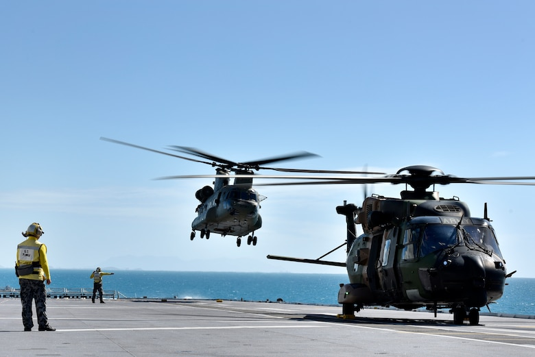 Australian Royal Navy Leading Seamans Timu and Harrison work on the flight deck with MRH90 and CH-53 helicopters during Exercise Sea Explorer aboard the HMAS Canberra at Sea June 9, 2018. The helicopters and soldiers were practicing rescue and recovery missions as part of the overall Ex Sea Series 18. The series is designed to train Australian Forces and get them amphibious ready. U.S. Marines and Sailors with Marine Rotational Force - Darwin 18 are working alongside the Australian Defence Force as part of the Amphibious Task Group.