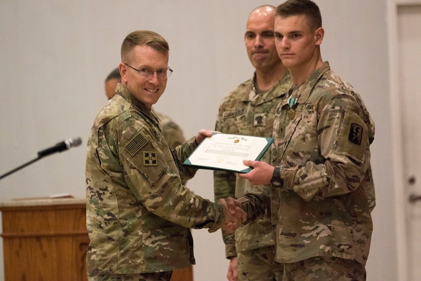 U.S. Army Maj. Gen. David C.Hill, U.S. Army Central'sdeputy commanding general,presents an award to Spc. Jacob T. Randall, the enlisted Soldier winner of USARCENT's Best Warrior Competition. The purpose of the Best Warrior Competition is to promote morale, improve cohesion between units and reinforce the importance of individual excellence within the Army profession.