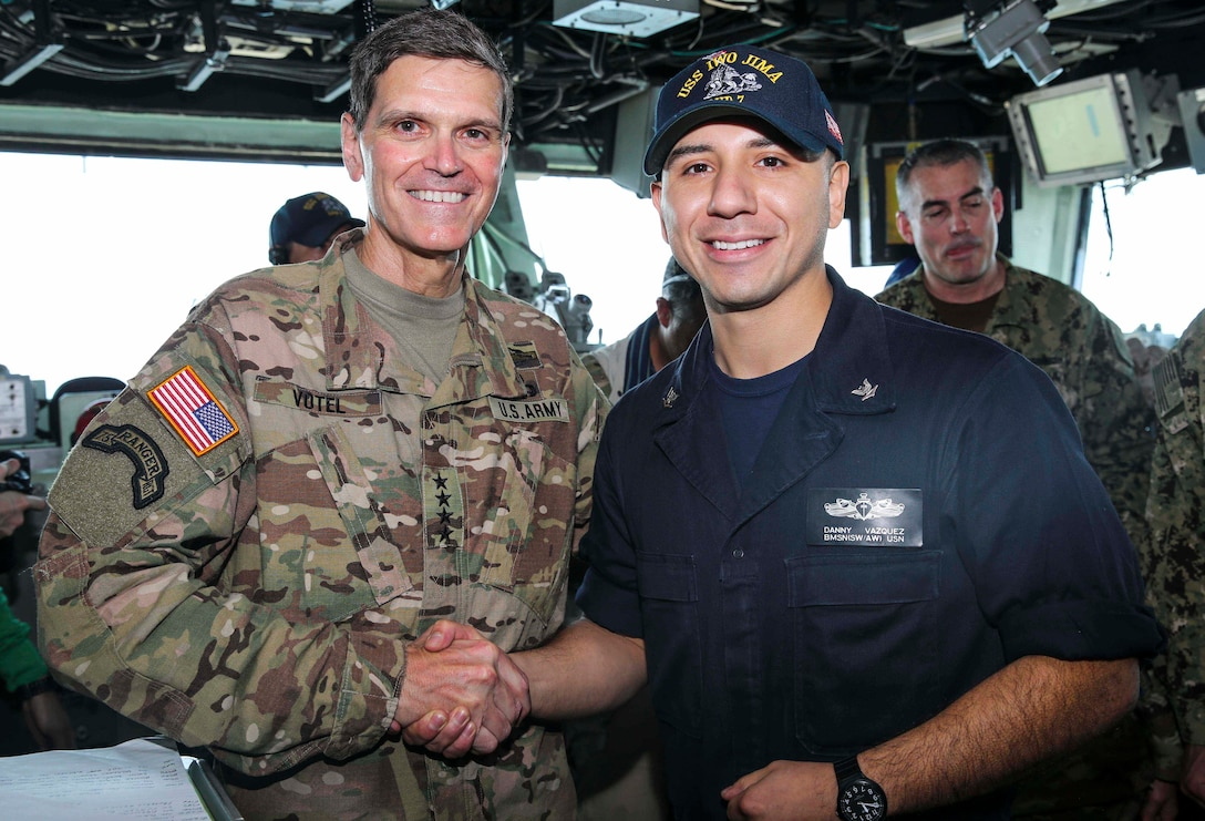 U.S. Army Gen. Joseph Votel, commander, U.S. Central Command, poses for a picture with U.S. Navy Boatswain's Mate 3rd Class Danny Vazquez  aboard the Wasp-class amphibious assault ship USS Iwo Jima (LHD 7), June 22, 2018. Votel, Vice Adm. Scott Stearney, commander, U.S. Naval Forces Central Command, and other distinguished visitors took a tour of Iwo Jima and spoke with crew members and Marines with the 26th Marine Expeditionary Unit, who are currently deployed to the U.S. 5th Fleet of operations in support of maritime security operations to reassure allies and partners and preserve the freedom of navigation and the free flow of commerce in the region. (U.S. Marine Corps photo by Cpl. Jon Sosner/Released)