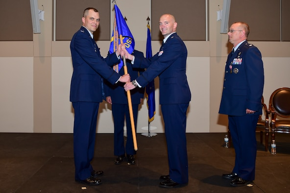 Lt. Col. Jason McCandless, 460th Operations Support Squadron commander, center, receives the guidon from Col. Robert Hutt, 460th Operations Group commander during a change of command ceremony June 28, 2018, on Buckley Air Force Base, Colorado. The changing of the guidon symbolizes the official change of command. (U.S. Air Force photo by Airman 1st Class Jake Deatherage)