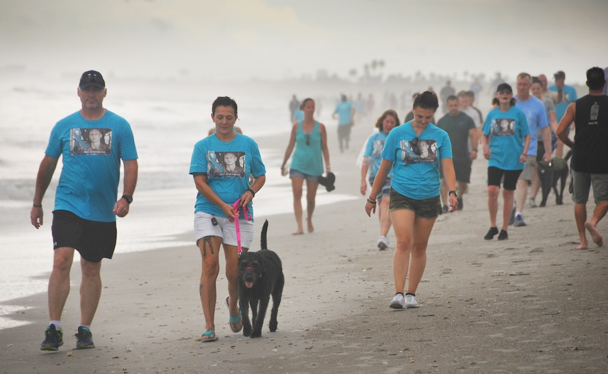 Air Force veteran Stacey Pavenski, center, 46, of Palm Bay, Florida, walks on the beach with her therapy dog, Memphis Belle. Pavenski is on a journey to bring awareness to PTSD and traumatic brain injury disorders that lead 22 veterans a day to take their own lives. Her husband Air Force Master Sgt. Pete Pavenski took his own life Sept. 18, 2018. To help with the healing process, Pavenski joined forces with Mission 22, a non-profit organization, to put together a PTSD 3K walk-run on Florida's Space Coast during PTSD Awareness Month June 30. Approximately 300 people registered for the walk. (Courtesy Malcolm Denmark)