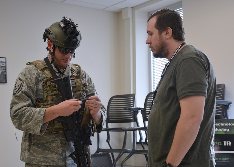 Battle Sight Technologies LLC President, Nick Ripplinger (right) shows a member of the Explosive Ordnance Disposal team the Marking Appliance Reusable Chemiluminsence, or MARC, during a Tech Warrior Ops event in Fairborn, Ohio. The company licensed the technology from the Air Force Research Laboratory Materials & Manufacturing Directorate and demonstrated it at the event. (Courtesy photo)