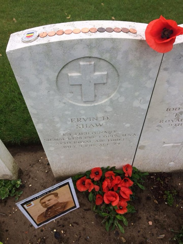 A photo of Royal Canadian Air Force 1st Lt. Ervin David Shaw, 48th Squadron Bristol F2B Brisfit pilot, is placed next to his grave at Regina Trench Cemetery, Courcelette, Somme, France, circa May 2018.